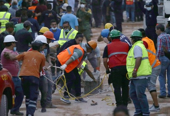 Volunteers and rescue personnel work on the remains of a collapsed primary school after a 7.1 earthquake struck Mexico City, Tuesday, Sept. 19, 2017. Rescue workers are toiling frantically in an attempt to find children they believe are trapped under the rubble. (AP Photo/Marco Ugarte)