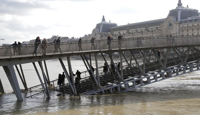 People watch the Seine river from the Leopold-Sedar-Senghor bridge in Paris, France, Friday, Jan. 26, 2018 The Paris region has been deeply affected by the floods that hit the country over the past week, but in Paris, it was business as usual. (AP Photo/Michel Euler)