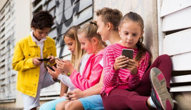 Παιδιά παίζουν με τα κινητά τους