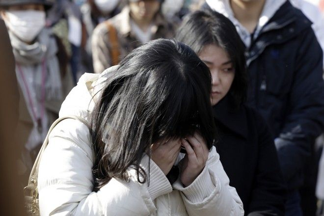 A woman cries as she mourns the victims of the March 11, 2011 earthquake and tsunami during a special memorial event in Tokyo, Saturday, March 11, 2017. Japan on Saturday marked the sixth anniversary of the 2011 tsunami that killed more than 18,000 people and left a devastated coastline along the country's northeast that has still not been fully rebuilt. (AP Photo/Eugene Hoshiko)