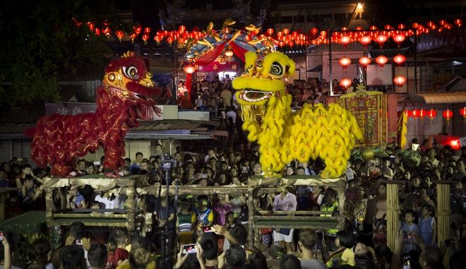 A Lion Dance is performed outside a Chinese temple during the 6th days of Chinese Lunar New Year in Penang, Malaysia, Tuesday, Feb. 20, 2018. Chinese around the world celebrated the Year of Dog in the Chinese lunar calendar. (AP Photo/Vincent Thian)