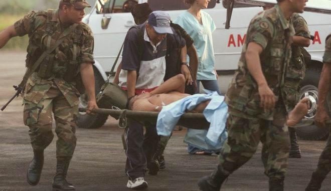Soldiers carry a comrade wounded  during fighting with rebels of the Revolutionary Armed Forces of Colombia, FARC, to an ambulance at the airport in Florencia, in southern Colombia, Monday, Feb. 25, 2002. Clashes between the rebels and government forces have been occurring near Florencia. (AP Photo/Ricardo Mazalan)