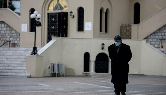 Πιστός με μάσκα έξω από εκκλησία