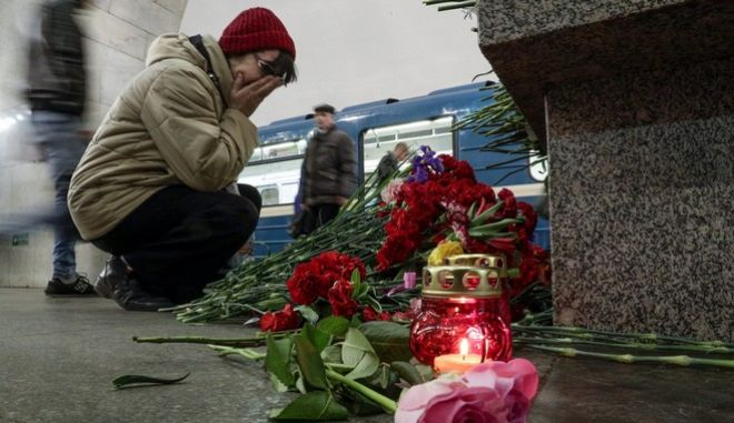 A woman reacts as she lays flowers at a symbolic memorial at Tekhnologichesky Institute subway station in St. Petersburg, Russia, Tuesday, April 4, 2017. A bomb blast tore through a subway train deep under Russia's second-largest city St. Petersburg Monday, killing several people and wounding many more in a chaotic scene that left victims sprawled on a smoky platform. (AP Photo/Dmitri Lovetsky)