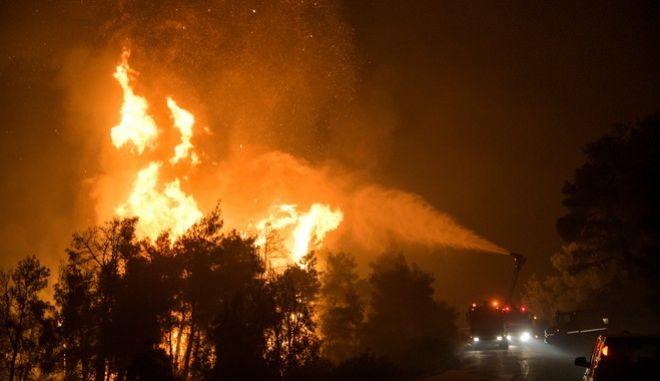 Πυροσβέστες προσπαθούν αργά το βράδυ της Τρίτης να περιορίσουν την μεγάλη πυρκαγιά που κατακαίει από τις 3 τα χαράματα της Τρίτης 13 Αυγούστου 2019, την περιοχή Μεσσαπίων-Δίρφυος. Η πυρκαγιά έχει τρία μέτωπα τα οποία εκτείνονται στα 11,5 χιλιόμετρα.