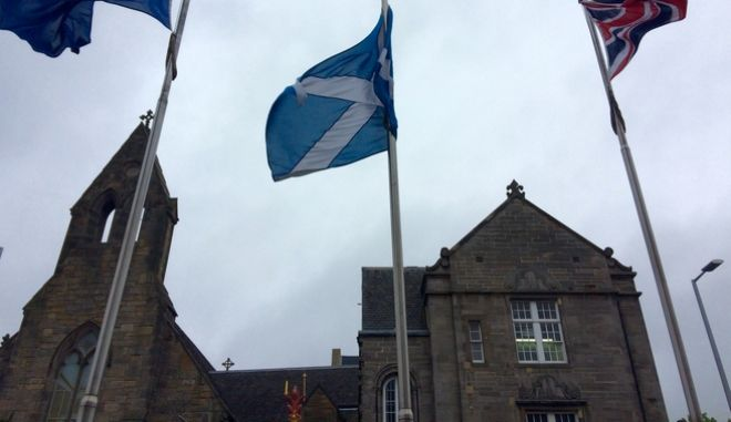 In this picture taken on Thursday, May 26, 2016, an EU flag, a Scottish flag and an Union Jack, left to right, wave outside Scottish parliament in front The Queens Gallery in Edinburgh. Scottish voters who want Britain to remain part of the EU would be so unhappy if it decided to break away that they would back a second referendum on forming their own independent nation. (AP Photo/ Dorothee Thiesing)