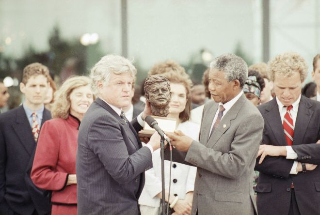 Nelson Mandela receives a bust of the late president John F. Kennedy from the president's brother Sen. Edward Kennedy, left, during a ceremony at the John F. Kennedy library in Boston Saturday, June 23, 1990.  At far right is Jacqueline Kennedy Onassis.  Eunice Shriver, sister of Sen. Kennedy looks on behind Mandela.  At right is Joe Kennedy II, son of Robert Kennedy.   (AP Photo/Charles Krupa)