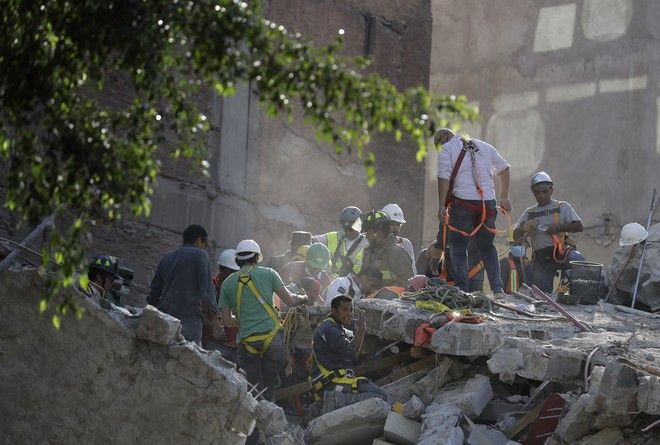 A man calls for a gas mask as rescue workers search for people trapped in the rubble of a collapsed building in the Condesa neighborhood of Mexico City, Tuesday, Sept. 19, 2017. A 7.1 earthquake stunned central Mexico, killing more than 100 people as buildings collapsed in plumes of dust.(AP Photo/Rebecca Blackwell)