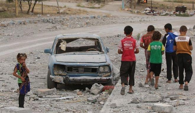 Συρία, παιδιά περπατούν δίπλα από ένα κατεστραμμένο αυτοκίνητο