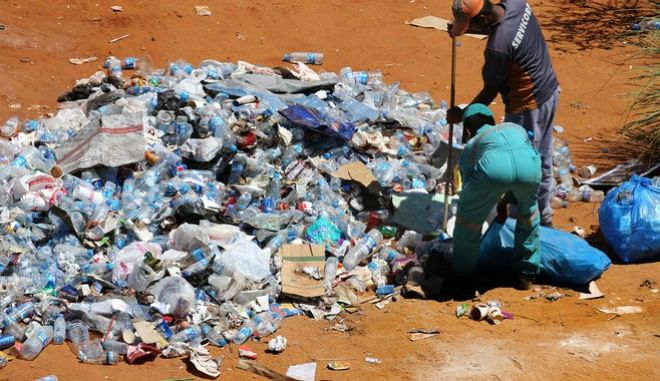 Asian workers who work for a Lebanese waste management company remove plastic bottles, at a square where Lebanese anti-government protesters hold their daily demonstrations, in downtown Beirut, Lebanon, Friday, Aug. 28, 2015. Beirut has been jolted by daily protests for the past week, including two massive demonstrations that turned violent over the weekend. (AP Photo/Hussein Malla)