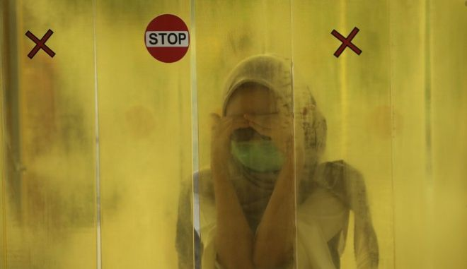 Πλάνο από Ινδονησία. Γυναίκα μέσα σε δωμάτιο φοράει μάσκα για τον κορονοϊό