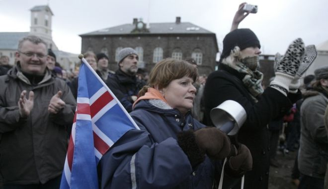 """A woman holds a flag of Iceland as she gathers during a peaceful protest near Iceland's Parliament house in Reykjavik January 24, 2009. A day after saying he would quit, Iceland's Prime Minister Geir Haarde voiced """"contempt"""" on Saturday for some of the actions by banks that triggered the country's economic collapse. Iceland, one of the richest countries in the world in 2007, plunged into crisis in October when it fell victim to the global credit crunch. Its currency collapsed as its financial system imploded. To stay afloat, it negotiated a $10 billion aid package crafted by the International Monetary Fund and effectively froze trade in its currency.    REUTERS/Ints Kalnins (ICELAND)"""