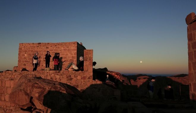 Arab tourists, left and American tourists, right, watch the sun as it rises and the moon as it sets from the view on top Mount Sinai or 'Mount Moses' in Saint Catherine in the Sinai peninsula, Egypt, Friday, Oct. 6, 2017. (AP Photo/Nariman El-Mofty)