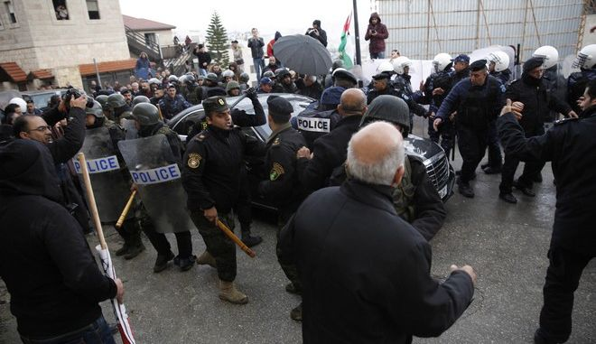 Palestinian security forces push away demonstrators from the convoy of Greek Orthodox Patriarch of Jerusalem Theophilos III, during a protest against his visit the Church of the Nativity, in the West Bank city of Bethlehem, Saturday, Jan. 6, 2018. (AP Photo/Majdi Mohammed)