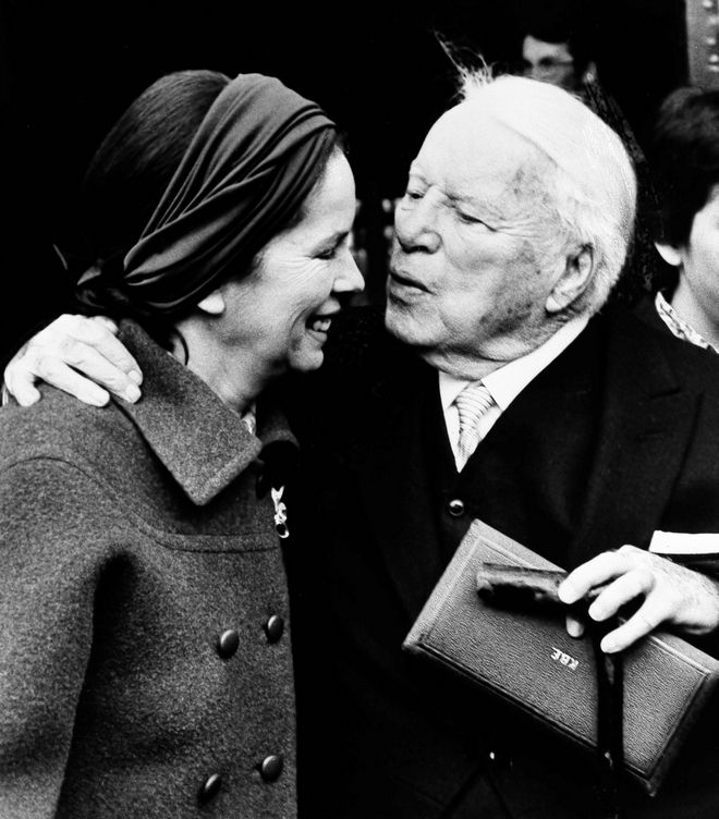Actor Charlie Chaplin kisses his wife Oona outside of Buckingham Palace in London, March 4, 1975, after being knighted by Queen Elizabeth II in a private ceremony.  In his hand is the box containing the insignia of Knight Commander of the Most Excellent Order of the British Empire.  (AP Photo)