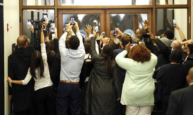 People rush the doors of the jury assembly room as former President Barack Obama departs after being dismissed from jury duty in the Daley Center on Wednesday, Nov. 8, 2017, in Chicago. For his time served, Obama is in line to be paid $17.20. (AP Photo/Charles Rex Arbogast)