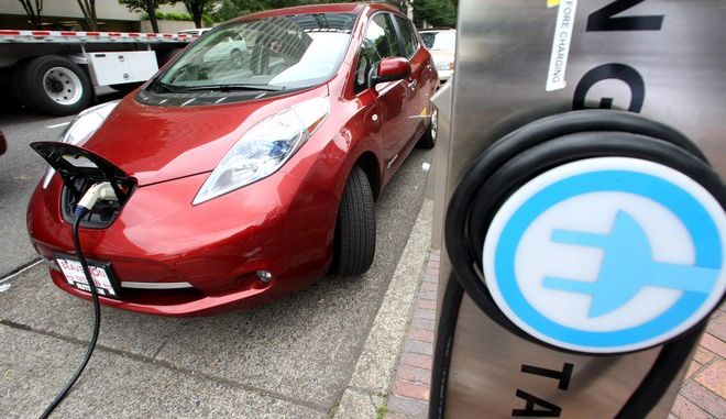 File-This Aug. 18, 2011 file photo shows a Nissan Leaf charges at an electric vehicle charging station in Portland, Ore. he governors of eight states including California and New York pledged Thursday to get 3.3 million zero-emission vehicles on roadways by 2025 in an effort to curb greenhouse gas pollution.  (AP Photo/Rick Bowmer,File)
