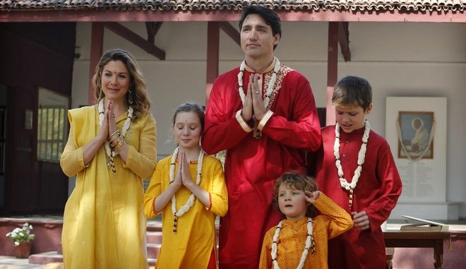 """Canadian Prime Minister Justin Trudeau, center, his wife, Sophie Gregoire Trudeau, their sons Hadrien, second from right, and Xavier, daughter Ella-Grace, second from left,  greet media in an Indian style of """"Namasteas"""" during their visit of Sabarmati Ashram or Mahatma Gandhi Ashram in Ahmadabad, India, Monday, Feb. 19, 2018.  Trudeau is in India for a weeklong visit with his family and aimed at enhancing business ties between the two countries. (AP Photo/Ajit Solanki)"""