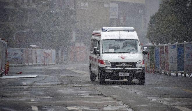 Ασθενοφόρο οδηγεί κατά μήκος ενός δρόμου κατά τη διάρκεια  χιονόπτωσης στο Xiaogan στην επαρχία Hubei της κεντρικής Κίνας