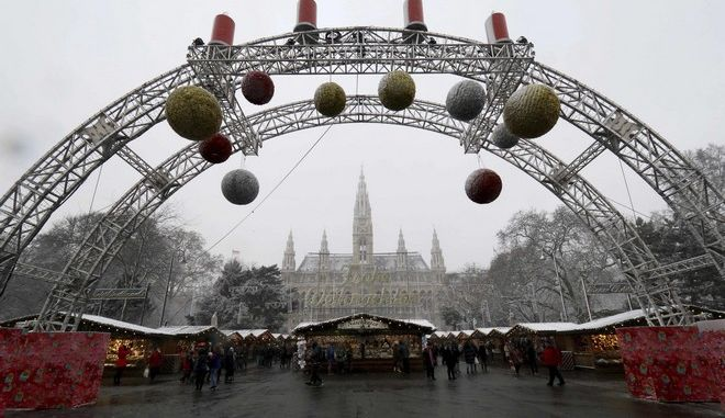 People walk at the Christmas Market in front of the city hall with the Christmas tree in Vienna, Austria, Tuesday, Dec. 20, 2016. (AP Photo/Ronald Zak)