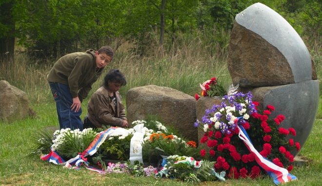 Romany children lean over a stony memorial during a ceremony of commemoration on the site of the former concentration camp in Lety near Pisek, Czech Republic, Tuesday, May 13, 2003. The war-time Czech administration (1939-45) held over 1,300 Romanies in Lety during the World War II. A total of 326 of them, including 241 children, did not survive. (AP Photo/CTK, David Veis)