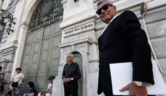 People queue outside the National Bank of Greece to withdraw cash, at the first day open banks despite the capital controls, in Athens, July 20, 2015 / O       ,       ,           ,  , 20 , 2015