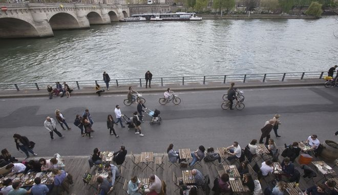 People relax at a brasserie along the Seine river in Paris, France, Sunday, April 2, 2017. The mayor of Paris Anne Hidalgo has unveiled a new car-free zone along the Seine river to fight against pollution. (AP Photo/Michel Euler)