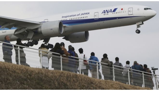People enjoy watching a Japanese carrier All Nippon Airways' plane landing at the Narita International Airport from a popular viewing spot at Sakuranoyama Park in Narita, east of Tokyo, Saturday, March 14, 2015. (AP Photo/Koji Sasahara)