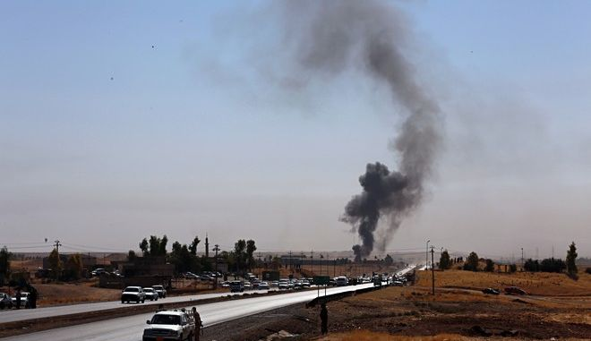 """Smoke rises while Iraqi security forces use bombs as Kurdish security forces withdraw from a checkpoint in Altun Kupri, outskirts of Irbil, Iraq, Friday Oct. 20, 2017.  A Baghdad court issued an arrest warrant for the vice president of Iraq's autonomous northern Kurdish region on Thursday for saying that Iraqi forces had """"occupied"""" the disputed province of Kirkuk this week.(AP Photo/Khalid Mohammed)"""