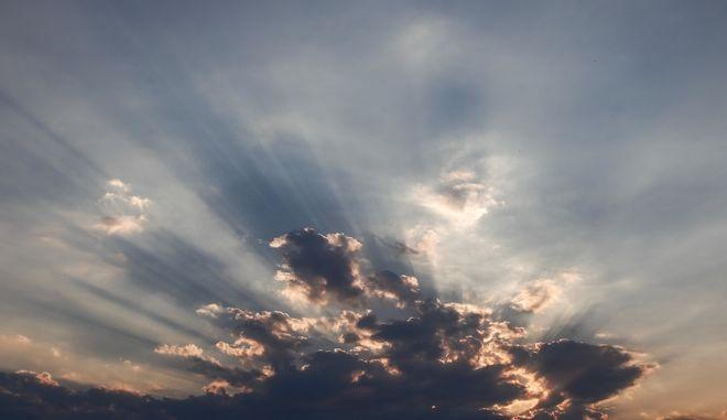 Οι ακτίνες του ηλίου ξεπροβάλουν μέσα από τα σύννεφα