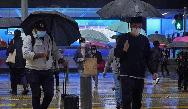 Διερχόμενοι σε δρόμο του Χονγκ Κονγκ με μάσκες λόγω κορονοϊού