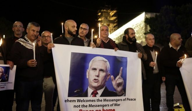 Palestinians hold posters showing US Vice President Mike Pence during a protests against his visit near the Church of the Nativity in the West Bank city of Bethlehem, Sunday, Dec. 17, 2017. (AP Photo/Mahmoud Illean)