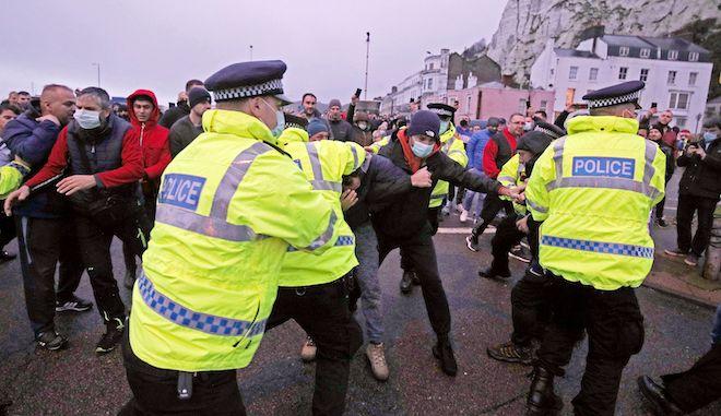 Η αστυνομία συγκρατεί τους οδηγούς που προσπαθούν να εισέλθουν στο λιμάνι του Ντόβερ στο Κεντ, αφού οι γαλλικές αρχές ανακοίνωσαν την άρση της απαγόρευσης με επίδειξη αρνητικού τεστ κορονοϊού, 23 Δεκεμβρίου 2020