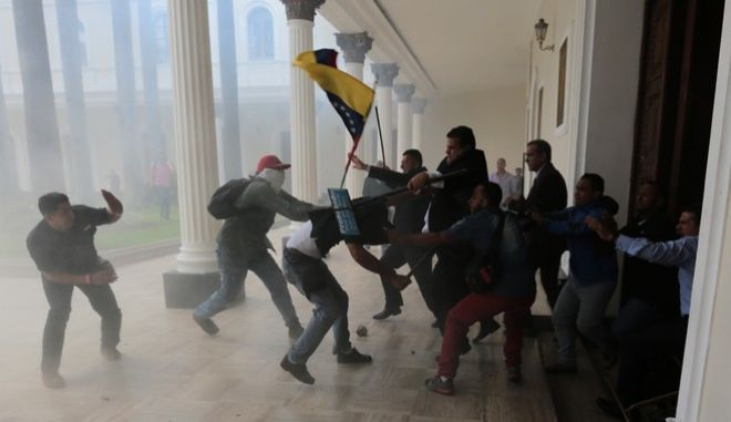 Opposition lawmakers brawl with pro-government militias who are trying to force their way into the National Assembly during a special session coinciding with Venezuelas independence day, in Caracas, Wednesday, July 5, 2017. At least five lawmakers were injured in the attack. Despite the violence, lawmakers later approved a plan by the opposition to hold a symbolic referendum July 16 to give voters the chance to reject President Nicolas Maduros plans to draft a new political charter. (AP Photos/Fernando Llano)
