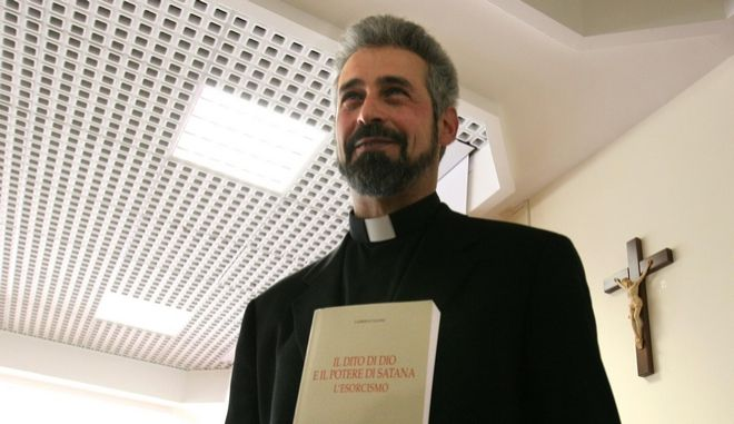 "Italian exorcist father Gabriele Nanni holds his book "" The Finger of God and the Power of Satan, the Exorcism"" after giving his lesson on Satanism for clergy at Rome's Regina Apostolorum Pontifical Academy, Thursday, Feb. 17, 2005.  Worried about  the lure of the devil, the Vatican-linked university, debuted its latest course offering a class on Satanism, black magic and exorcism. (AP Photo/Alessandra Tarantino)"