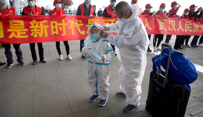 Ταξιδιώτες φορούν μάσκες προσώπου και στολές για προστασία από τον κορονοϊό στο Διεθνές Αεροδρόμιο της Wuhan, 8 Απριλίου 2020.