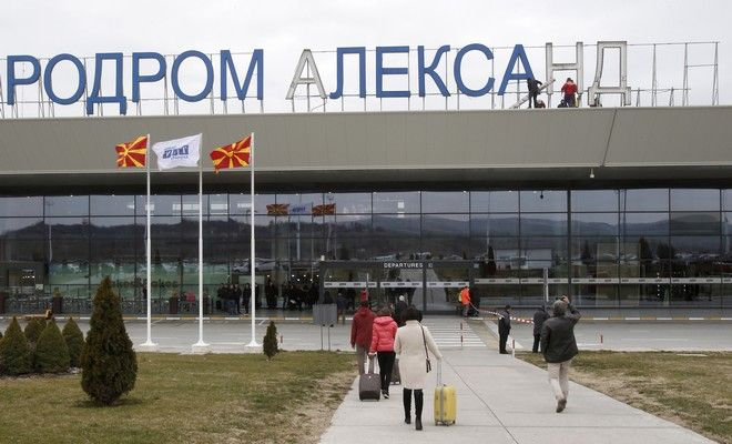 "Passengers walk towards the airport building, as workers remove giant letters of the sign, reading in Macedonian, ""Alexander the Great Airport"", near Macedonia's capital Skopje, Saturday, Feb. 24, 2018. The Macedonian government decided recently to rename the country's main airport which carried the name of the ancient warrior king Alexander the Great, as Skopje International Airport, in a goodwill gesture toward neighboring Greece. (AP Photo/Boris Grdanoski)"