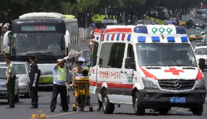 Ambulance attendants prepare to takes away a traffic warden hit by an unmarked car speeding on a lane reserved for delegates attending the China-Arab Cooperation Forum along a heavily policed road in Beijing, China, Thursday, June 5, 2014. (AP Photo/Ng Han Guan)