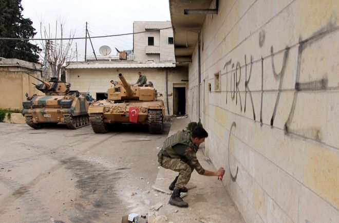 """A Turkish soldier writes """"Turkey"""" on a wall, near to tanks in position, in the city center of Afrin, northwestern Syria, Sunday, March 18, 2018. Turkey's president said Sunday the Turkish military and allied Syrian forces have taken """"total"""" control of the town center of Afrin, a major development in the nearly two-months offensive against a Syrian Kurdish militia that controls the area. (Hasan Krmzita/DHA-Depo Photos via AP)"""