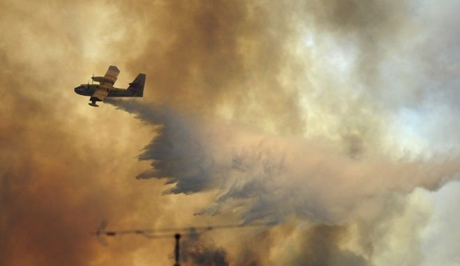 A fire fighting aircraft drops water over a fire outside the village of Pedrogao Grande central Portugal, Monday, June 19, 2017. More than 2,000 firefighters in Portugal battled Monday to contain major wildfires in the central region of the country, where one blaze killed dozens of people, while authorities came under mounting criticism for not doing more to prevent the tragedy. (AP Photo/Paulo Duarte)