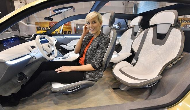 A model sits in the Skoda VISION E concept car at a preview of the Motor Show in Essen, Germany, Wednesday, Nov. 29, 2017. The international car performance festival starts Friday for the 50th time in the fair halls in Essen. (AP Photo/Martin Meissner)
