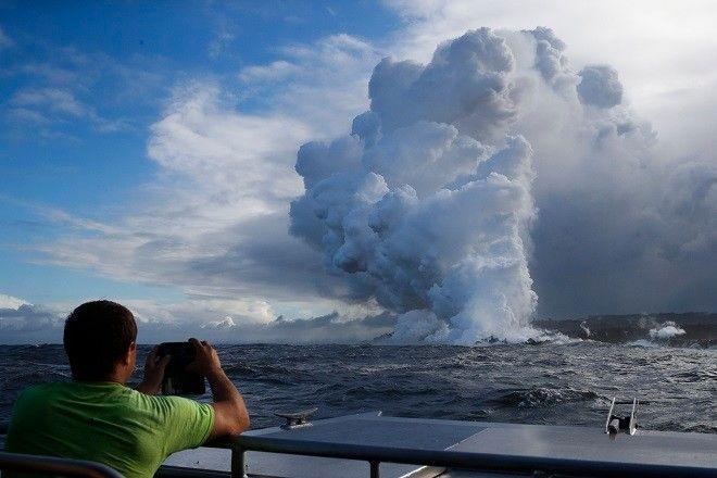 Ηφαίστειο Κιλαουέα. Τουρίστες σπεύδουν με μικρά σκάφη στην περιοχή όπου η λάβα συναντά τον Ωκεανό για να φωτογραφίσουν με κινητά τηλέφωνα τη σπάνια εικόνα.