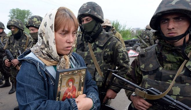 A resident holding a religious icon stands next to Ukrainian soldiers at a checkpoint which they seized in the early morning in the village of Andreevka, 7 kms from the centre of the southern Ukrainian city of Slavyansk, on May 2, 2014. Ukraine's military lost two helicopters and two servicemen on May 2 in a deadly offensive launched just before dawn against pro-Russian rebels holding the flashpoint town of Slavyansk, insurgents and authorities said. AFP PHOTO / VASILY MAXIMOVVASILY MAXIMOV/AFP/Getty Images