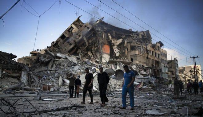 Παλαιστίνιοι περπατούν ανάμεσα στα ερείπια στην πόλη της Γάζας