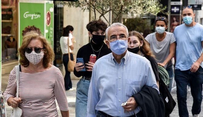 Κόσμος με μάσκα σε εξωτερικό χώρο
