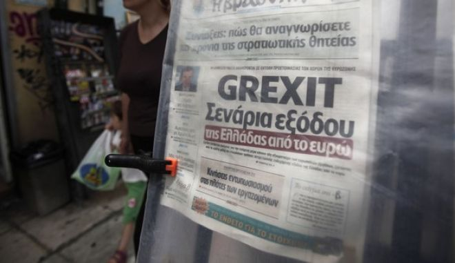 "A pedestrian passes a ""Grexit"" headline on a newspaper displayed at a street kiosk in Athens, Greece, on Thursday, May 24, 2012. European leaders tied their next steps on the financial crisis to the outcome of a bitterly contested election in Greece that may determine whether the 17-nation euro currency splinters. Photographer: Kostas Tsironis/Bloomberg via Getty Images"