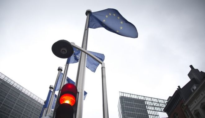 A red light flashes in front of an EU flag in front of EU headquarters in Brussels on Friday, June 24, 2016. Voters in the United Kingdom voted in a referendum on Thursday to decide whether Britain remains part of the European Union or leaves the 28-nation bloc. Results will be known later on Friday. (AP Photo/Virginia Mayo)