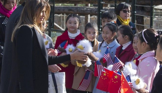 U.S. first lady Melania Trump hands out bald eagle dolls to Chinese children holding U.S. and Chinese flags near the Panda enclosure at the zoo in Beijing Friday, Nov. 10, 2017. (AP Photo/Ng Han Guan)