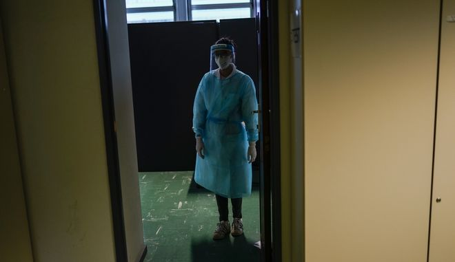 A medical worker, wearing a full protective gear, waits for travellers who arrived from abroad to be tested for COVID-19 in a Red Cross test center at Gare du Midi international train station in Brussels, Tuesday, Jan. 19, 2021. Belgium is strengthening its rules for travellers entering the country by train or bus in a bid to limit the spread of a more contagious variant of the coronavirus detected in Britain. (AP Photo/Francisco Seco)