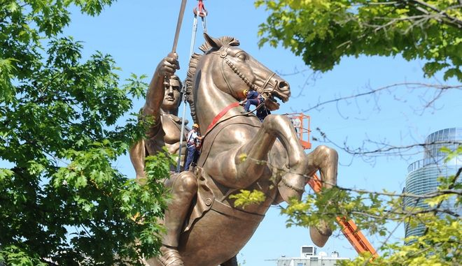 "Workers clamber over the statue as they prepare the controversial giant bronze statue of Alexander the Great astride his horse, Bucephalus, in the main square of the capital, Skopje, Tuesday June 21, 2011.  The 28-meter (92-foot) tall monument and fountain officially named ""Warrior on a horse"" cost some euro 9.4 million.  ( US $13.5 million), and claims Alexander the Great as an ancient local hero. (AP Photo/Dragan Perkovski)"